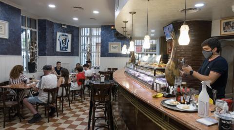 Un camarero del bar La Estrella sirve bebidas en el interior del local con varios clientes sentados.
