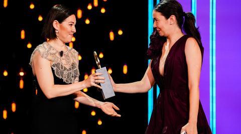 La directora y productora Alina Grigore (izda.) recibe la Concha de Oro de manos de la productora Gabi Suciu
