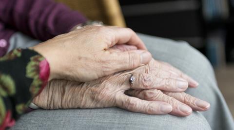 Imagen de las manos de una persona mayor junto a las de un ser querido.