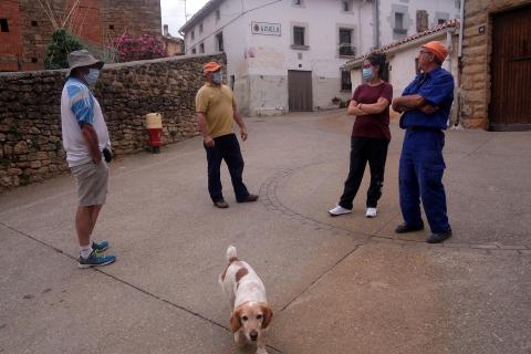 Los vecinos de Azuelo José Luis Rodríguez y su hija Nerea, a la derecha, conversan con el alcalde, Roberto Crespo, y otro vecino