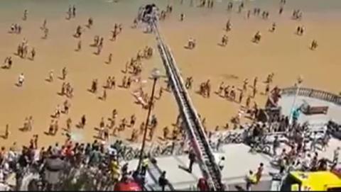 Los bomberos rescatan con una grúa a una mujer de la playa de La Concha