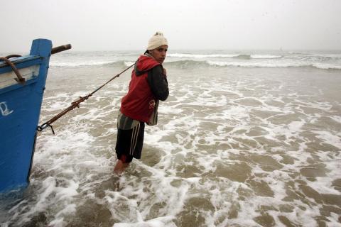 Salida de una patera desde la playa de Tarache