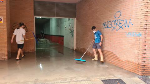 Varias personas achican agua en un garaje inundando de Tudela tras las fuertes lluvias de esta jornada