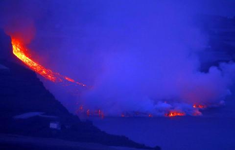 Momento en el que la colada de lava del volcán de La Palma llega al mar en la playa de Los Guirres.