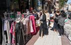 Varias personas observan la ropa expuesta a las puertas de una tienda de la céntrica Avenida de Zaragoza