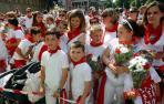 Los niños honran a San Fermín y lo rodean de flores rojas y blancas