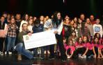 El niño Álex Berdonces y sus padres posan con el cheque y artistas que actuaron en la gala.