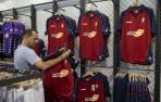 Un cliente examina la primera equipación de Osasuna, en la tienda de El Sadar, durante el verano.