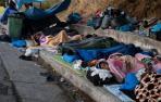 Migrantes del campo de Moria duermen junto a una carretera.
