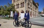 De izda a dcha: Hurtado, Leoz e Irujo, con una bici eléctrica, ante la antigua estación