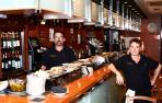 Eduardo Zubieta posa en la barra del bar StickBol repleta de pinchos junto a otro camarero.