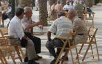 Un grupo de personas mayores conversa en un pequeño corro al aire libre