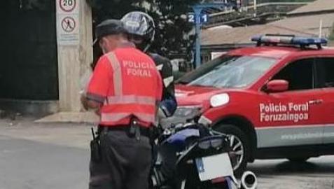 Imagen de un policía foral, con el motorista denunciado.