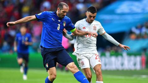 El veterano capitán italiano Giorgio Chiellini, pugna por el balón con Pedri
