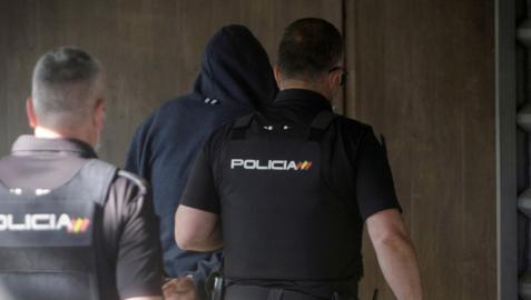 Agentes de la Policía Nacional conducen a uno de los detenidos (mayores de edad) al interior de los juzgados