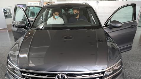 Un vendendor muestra un vehículo a unos posibles compradores en un concesionario.