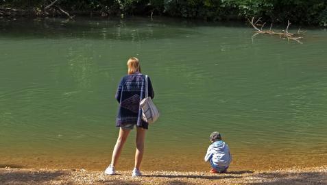 Una mujer y un niño, disfrutando del buen tiempo junto al río en Los Llanos de Estella