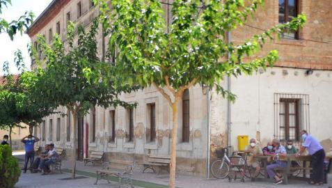 Varias personas descansan a la sombra junto al antiguo hospital de Falces