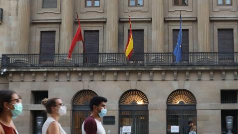 Varias personas caminan ante la fachada del Palacio de Navarra, sede del Gobierno foral, en la Avenida Carlos III