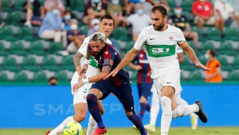 El delantero del Levante José Luis Morales (c) se escapa de Roco (i) y de Gonzalo Verdú, ambos del Elche, durante el partido de la quinta jornada de Liga en Primera División