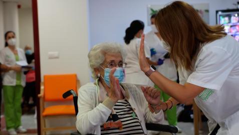 Una anciana de una residencia de ancianos celebra con una enfermera la tercera dosis de la vacuna contra el coronavirus