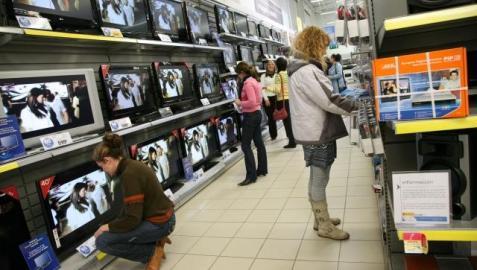 Varios clientes viendo televisiones y aparatos para poder ver la TDT, en un centro comercial. ARCHIVO