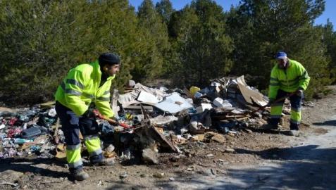 Dos trabajadores de la brigada de Lodosa recogen residuos en el pinar próximo a la fábrica de escayola. GENER
