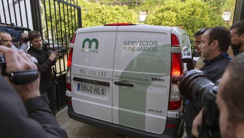 Un furgón de servicios funerarios se abre paso entre los reporteros para entrar en el Palacio de Dueñas en Sevilla.