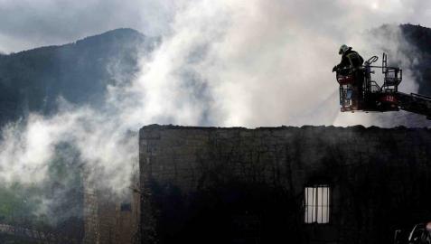 Bomberos del Gobierno de Navarra y agentes de la Policía Foral trabajan en el incendio que esta madrugada ha calcinado una vivienda en la localidad de Artaiz (Unciti).