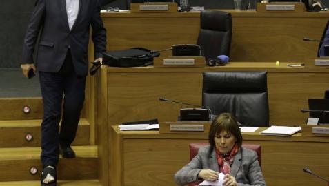 Martínez (Geroa Bai) baja las escaleras del hemiciclo entre Araiz (Bildu) y la presidenta Barkos.