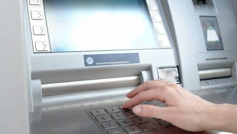 Una persona retira dinero de un cajero automático.
