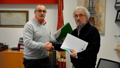 Valentín García (izda.) y Francisco Soto se dan la mano tras haber firmado el convenio.