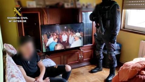 La guardia civil y el joven arrestado, en la vivienda donde estaba secuestrada la menor en Lugo.