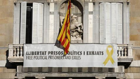 Vista del cartel reclamando la libertad de los líderes independentistas presos y un lazo amarillo en la fachada del Palau de la Generalitat.