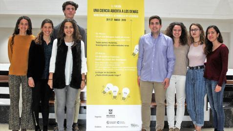 Los alumnos Reyes Hernández, Lucía Prado, María Pérez, Adrián Díaz.  Carlos Peña, Lucía Suárez, Celia Canseco y Sara Contreras, en una foto de familia tomada en la Universidad de Navarra junto al cartel que anuncia su logro.