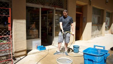 Un comerciante limpia las inmediaciones de su establecimiento tras las lluvias torrenciales del 8 de julio pasado