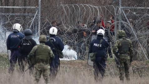 Un grupo de migrantes intenta de cruzar la frontera griega, mientras la policía trata de evitarlo lanzando botes de gases lacrimógenos