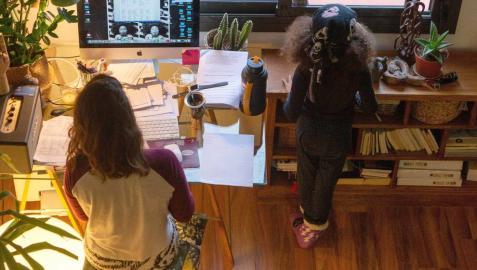 Una mujer realiza teletrabajo en su casa mientras su hija juega a su lado