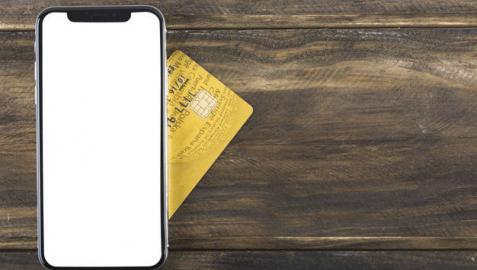 Imagen de un smartphone junto a una tarjeta de crédito