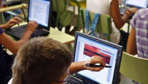 Varios niños utilizan ordenadores en un aula.