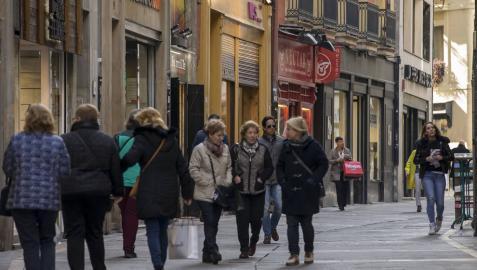 Varios grupos de personas pasean en la calle Zapatería, del Casco Viejo de Pamplona, con bolsas de compras.