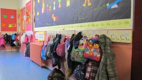 Mochilas y ropa en el perchero de un aula infantil.