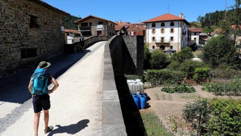 Imagen de un peregrino que cruza el Puente de la Rabia de Zubiri situado en el recorrido del Camino de Santiago