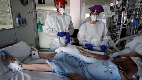 Profesionales de la UCI del CHN, junto a un enfermo de Covid.