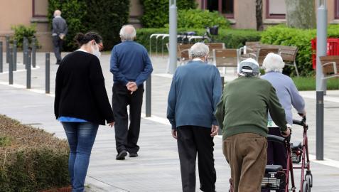 Un grupo de mayores pasea por el exterior de la residencia de la Casa de la Misericordia de Pamplona.