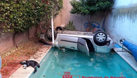 El coche, volcado, tras caer a la piscina.