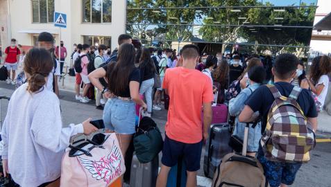 Varios estudiantes que se encontraban en cuarentena por el macrobrote de covid-19 en Mallorca aguardan a su llegada a la estación marítima para embarcar hacia Valencia