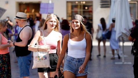 Dos jóvenes caminan sin mascarilla