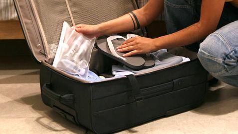 Una persona hace su equipaje en una maleta de mano.
