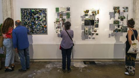 Varias personas observan distintas piezas creadas por  Leo Pum, obras que el artista realiza con objetos obsoletos mediante la técnica de la  técnica de la fotogrametría.